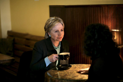 Hillary Clinton meets with  constituent as she held a cup of coffee during the 2008 presidential campaign. Photo by Brooks Kraft.