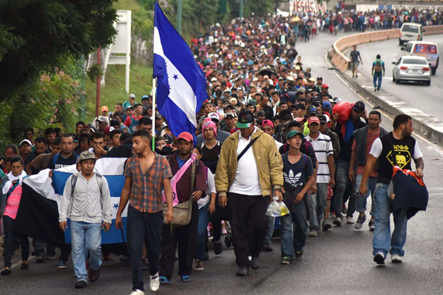A caravan of migrants fleeing Honduras approaches the Mexico-Guatemala border amidst a surge in border crossings on the U.S.-Mexico border, 17 October 2018. The caravan has grown to 4,000 people along the way. Photo: Orlando Estrada / NBC News
