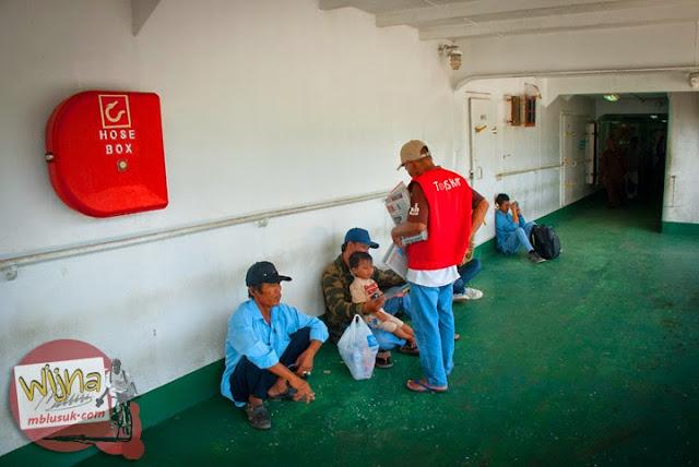 penumpang membeli koran bekas dari penjual di atas kapal Ferry Virgo 18 tujuan Pelabuhan Bakauheni, Lampung yang digunakan sebagai alas duduk