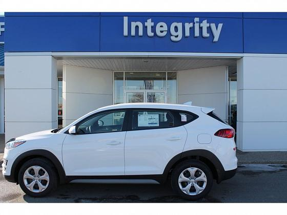 A 2019 white Tuscon Essential sits parked outside Integrity Hyundai in Lethbridge, AB