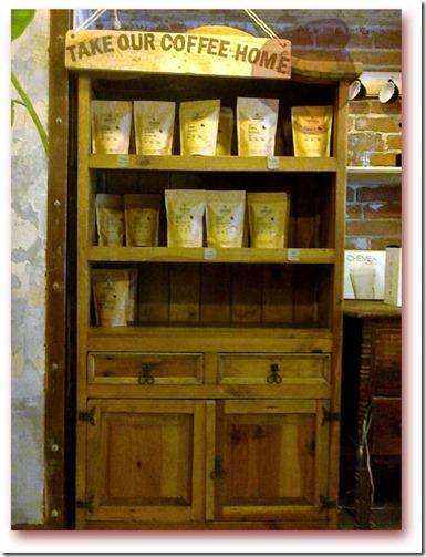 Foto do móvel expositor com pacotes de pó de café de várias origens (Kênia, Colômbia e Nigéria), à venda.