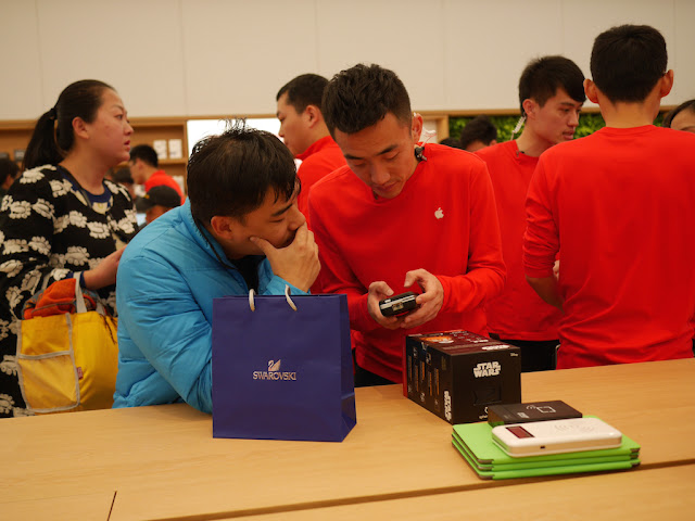 man with Swarovksi bag making a purchase at the SM Lifestyle Center Apple Store in Xiamen, China