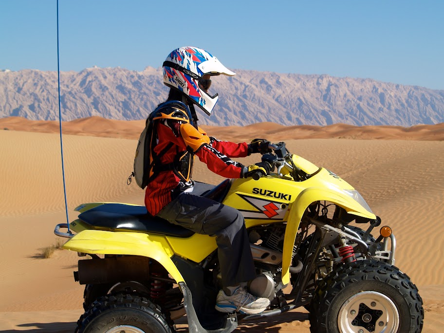 Young rider, Dar Rossetti, 12, wears protective gear while riding a Suzuki Quadrunner 250 in the dunes west of Jebel Hafeet, Al Ain