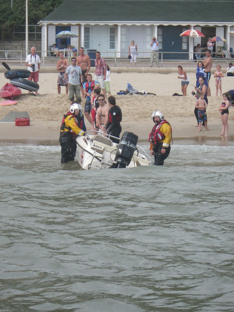 1 September 2012 -the crew members secure the righted motorboat.  Photo credit: Poole RNLI/Dave Riley