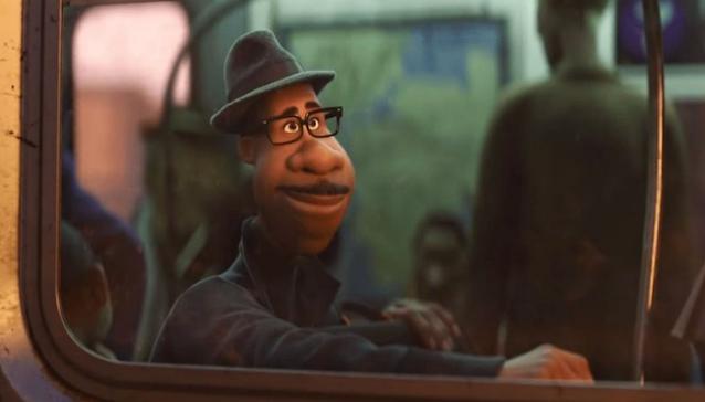 Homem negro, de óculos, chapéu coco, ele tem bigode e sorri. Ele está sentado dentro de um ônibus e está com uma dos braços na beira da janela, vemos ele a partir do lado de fora do ônibus.