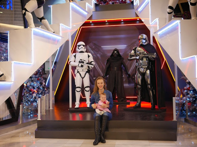 young woman with a baby posing for a photo in front of a Star Wars display at the IAPM shopping center in Shanghai