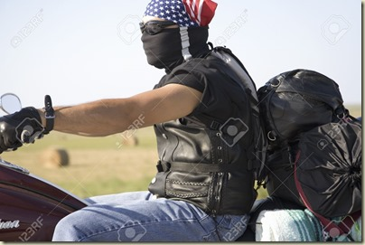 20490417-Motorcyclist-with-American-flag-bandana-driving-on-Interstate-Highway-90-heading-west-towards-Sturgi-Stock-Photo