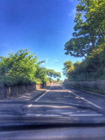 Photo of a road from the passenger side of a car in Scotland with blue skies and green trees at either side