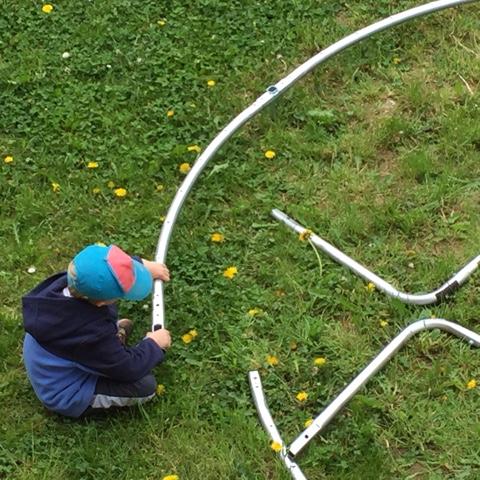Kind hilft beim Trampolinaufbau