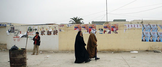 A man and a woman walk outside a polling station on election day in Iraq (2009). Photo: Rick Bajornas / UN Photo