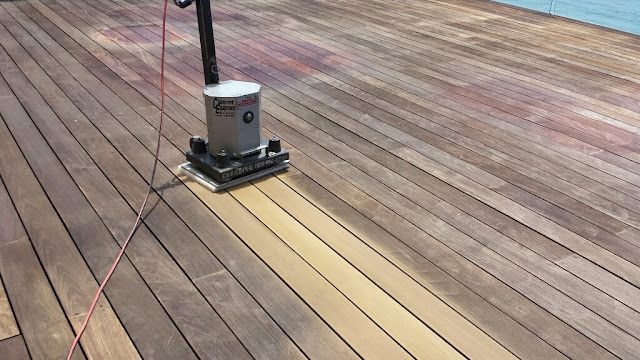 A heavy floor sander removes damaged wood and smooths out imperfections
