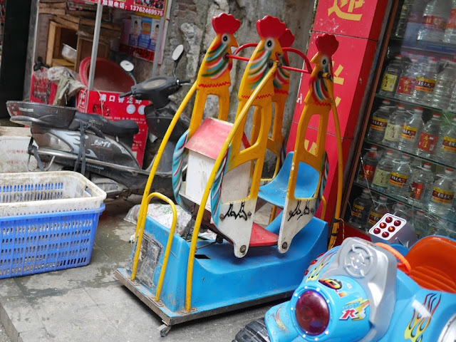 kiddie ride resembling a two-child swing with one seat filled by a house-like object