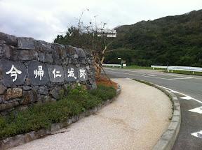 城跡の入口に向かって右側の県道115線を渡るとクバ御獄の案内板がある(画面中央右)