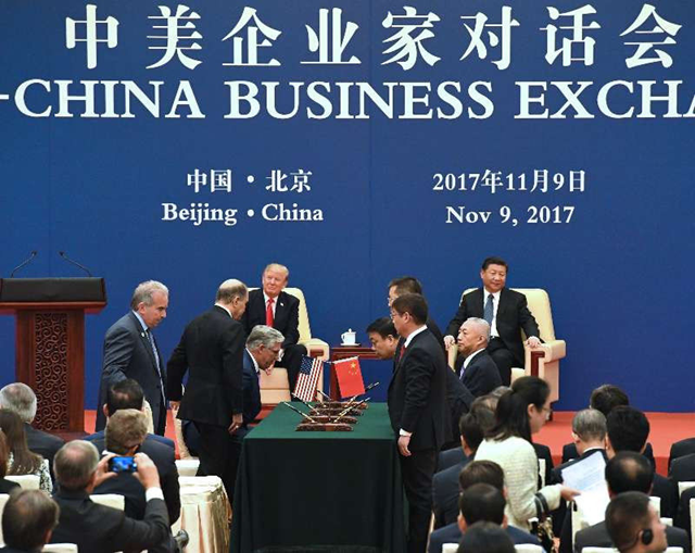Trump, seated at left rear, and Chinese President Xi Jinping, seated at right rear, watch as West Virginia Secretary of Commerce H. Wood Thrasher, sitting at left, and China Energy President Ling Wen, sitting at right, meet to sign a Memorandum of Understanding between China Energy and the state of West Virginia in Beijing today, 9 November 2017. The W.Va. project is part of the US-China Business Exchange trade mission to enhance relations between the two countries. The China Energy announcement in West Virginia was the largest investment in a series of projects in US corporations and other states totaling a reported $250 billion of investment in the U.S. Photo: WV Commerce