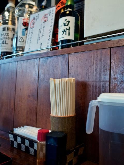店内のカウンター席。居酒屋らしく酒のボトルが並べられてる。