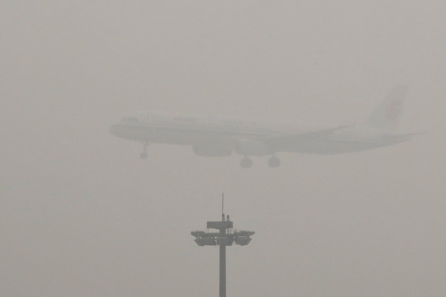 Heavy smog over Beijing International Airport in December 2016. The aviation industry may also be included in China's carbon-trading market. Photo: Andy Wong / Associated Press
