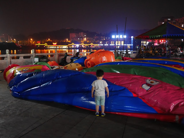 child looking at a deflated slide ride at Donghu Park in Zhuzhou, Hunan