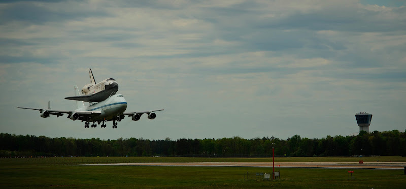Photo: Space shuttle Discovery, mounted atop a NASA 747 Shuttle Carrier Aircraft (SCA) approaches the runway at Washington Dulles International Airport, Tuesday, April 17, 2012, in Sterling, Va. Discovery, the first orbiter retired from NASA's shuttle fleet, completed 39 missions, spent 365 days in space, orbited the Earth 5,830 times, and traveled 148,221,675 miles. NASA will transfer Discovery to the National Air and Space Museum to begin its new mission to commemorate past achievements in space and to educate and inspire future generations of explorers. Photo Credit: (NASA/Paul E. Alers)
