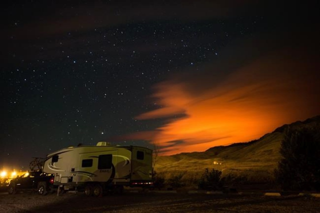 A trailer parked at a campground in Savona, B.C., is seen as the Elephant Hill wildfire burns in the distance near Clinton, illuminating smoke in the sky during the early morning hours of Sunday, 30 July 2017. Photo: Darryl Dyck / THE CANADIAN PRESS