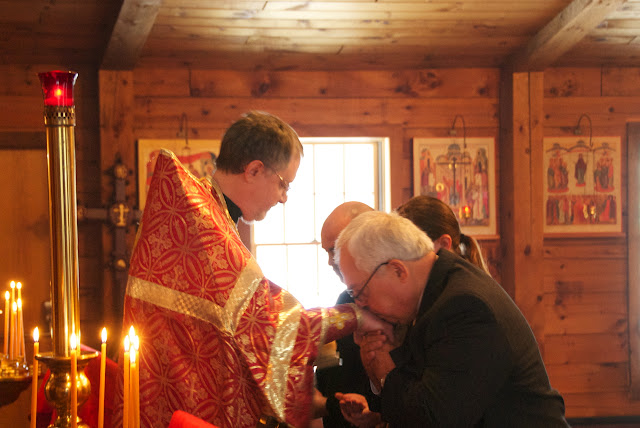 The candidates kiss the priest's hand upon receiving his blessing.