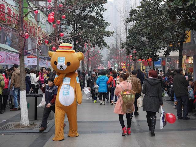 person wearing a bear suit walking down a busy pedestrian street