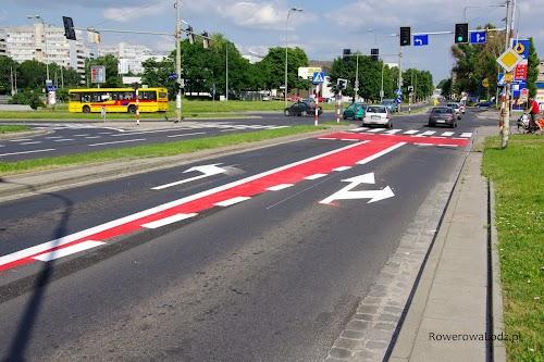 Inne skrzyżowanie i znów pas ruchu dla rowerów wciśnięty pomiędzy pasy dla samochodów. Na końcu śluza dla rowerów. Wszystko w wymowny kolorze ostrzegającym, że to miejsce zarezerwowane dla rowerzystów.