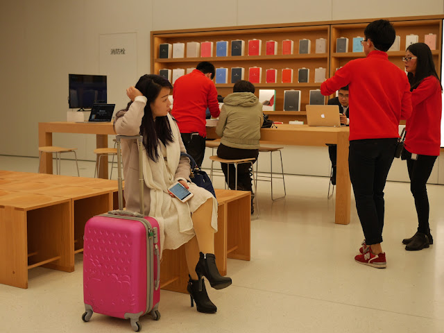 woman waiting with a suitcase at the SM Lifestyle Center Apple Store in Xiamen, China