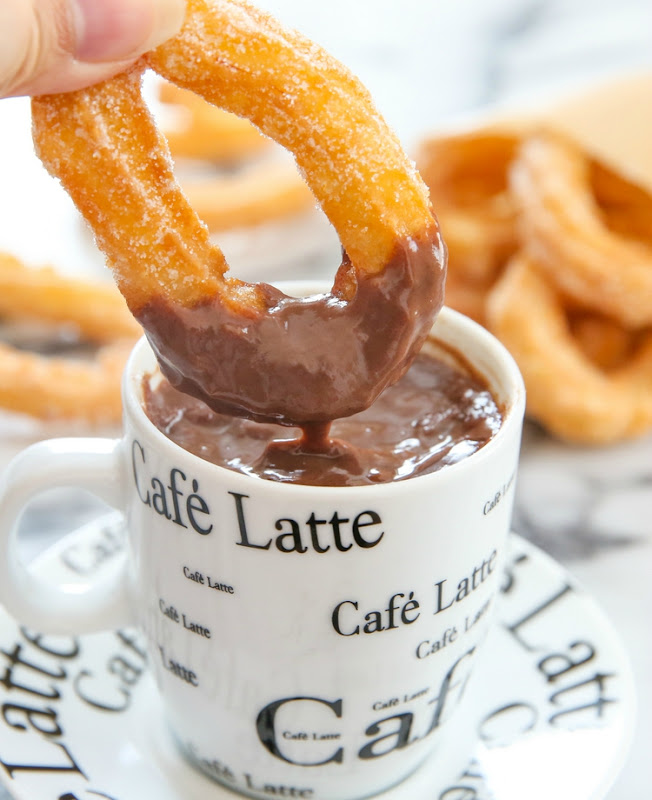 photo of a churro being dipped in a mug of chocolate