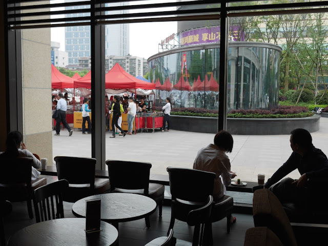 man and woman looking out a window at Starbucks in Hengyang