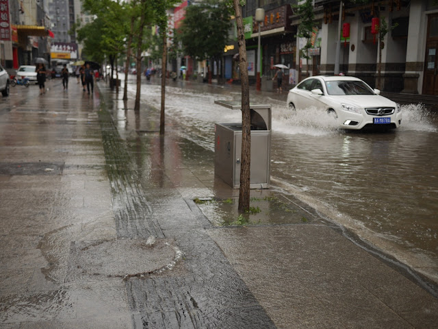 water coming out of a sewer hole on a sidewalk next to a flooded street in Taiyuan, China