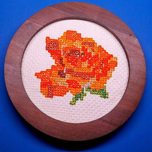orange rose cross-stitched on white monk's cloth
