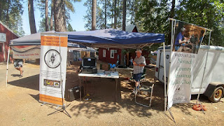 "ARES at Nevada County Fair.It is fair time in Nevada County. This year we are together with the Nevada County Amateur Radio club. Since Cal McKitrick is the president of the club AND a valued ARES member we get lots of exposure at the fair. We have a nice banner (orange in foreground) and always have an ARES member or two on hand for questions and information. ARES go boxes (on table in foreground) are good and drawing in some folks that like to ""geek"" out on the hardware. Thanks to Cal for letting us tag along!"