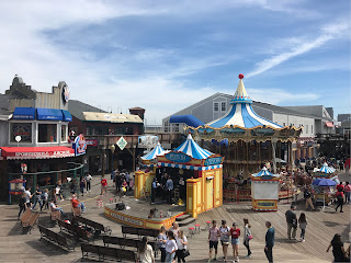 En liten scene og en karusell på brygga, flankert av noen butikker.