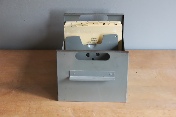 Gray metal file caddy with folders available for rent from www.momentarilyyours.com, $3.