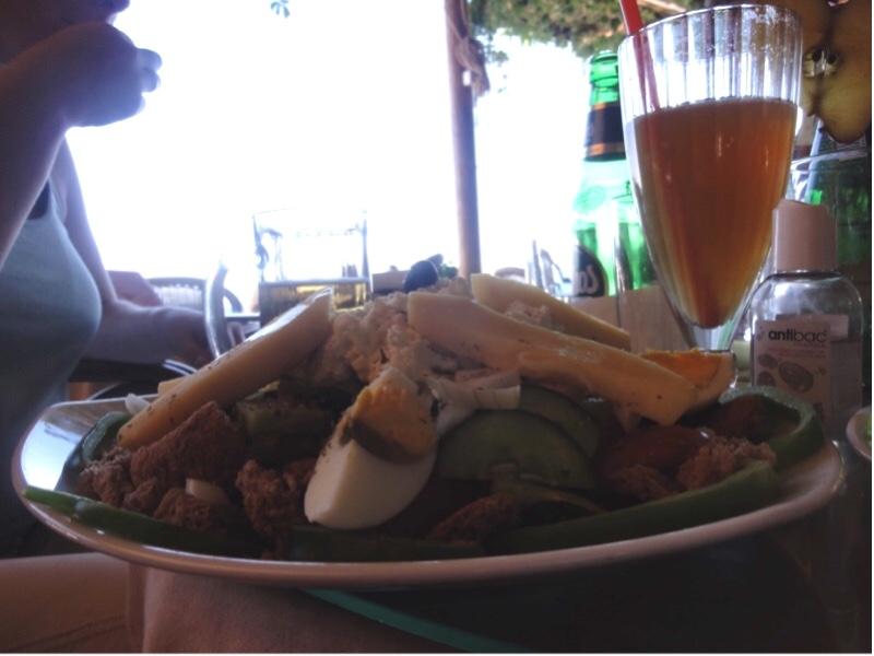 Tallerken med agurkskiver, brødbiter, paprika, potetbåter, egg med mer. Et glass med mørk eplejuice i bakgrunnen.