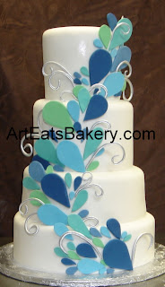 Custom designed green, blue, and teal sugar sculpture peacock four tier fondant wedding cake