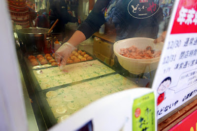 Sights of Osaka - Amerikamura - while waiting in line for takoyaki you can watch them being made fresh. First you pour in a batter into special takoyaki pans, and then add the seasoning and the little bits of octopus.