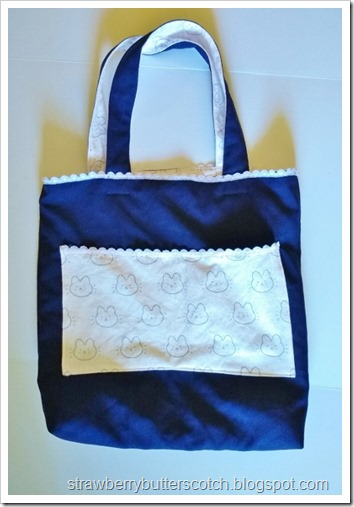 The finished navy blue bag with cute pink pockets, lining, and lace trim.