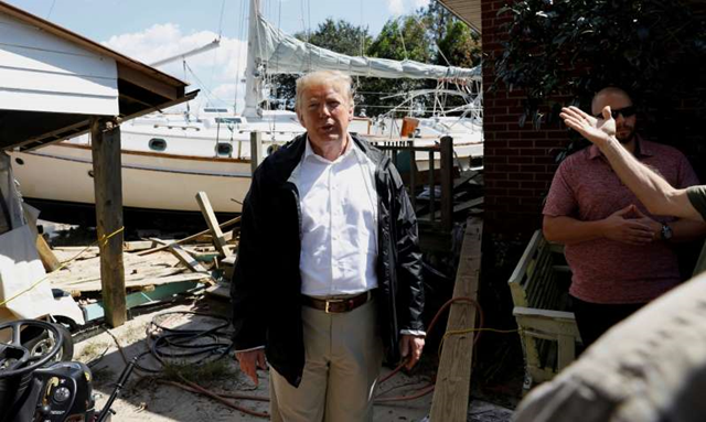 U.S. President Donald Trump participates in a tour of areas damaged by Hurricane Florence in New Bern, North Carolina, U.S., 19 September 2018. Seeing a boat beached in a resident's back yard, he said, 'At least you got a nice boat out of the deal.' Photo: Kevin Lamarque / REUTERS