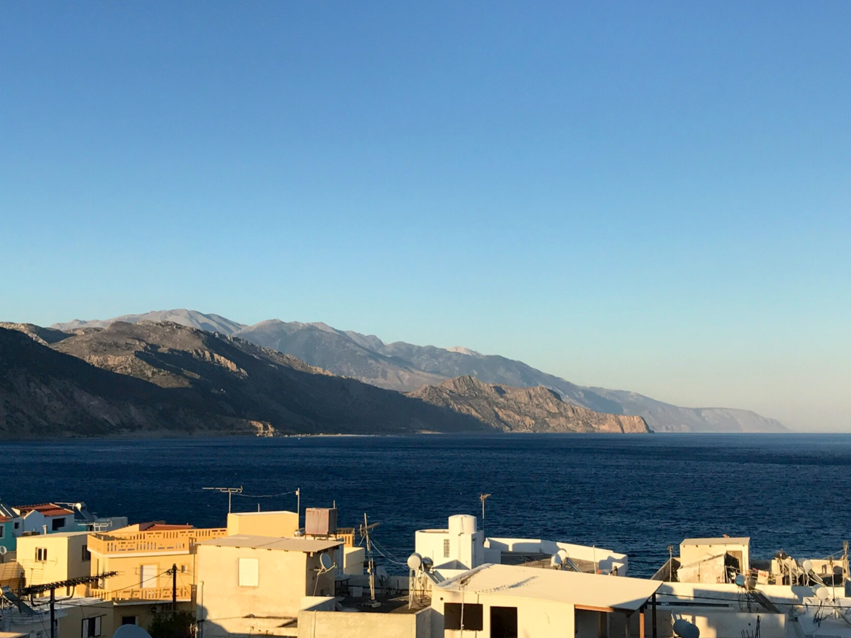 Utsikt over sjøen mot noen fjellsider i lavt sollys. Noen hustak i forgrunnen.