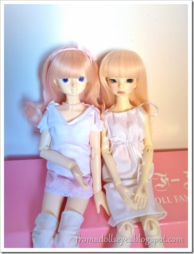 Two cute ball jointed dolls sitting together.