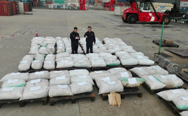 Customs officers stand guard over 3.1 tons of seized pangolin scales at a port in Shanghai, 28 December 2016. It is estimated that up to 7,500 of the endangered creatures may have been killed. Photo: AFP