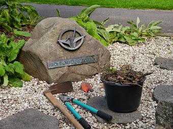 Gedenkstein mit Gartenwerkzeugen und Abfalleimer.
