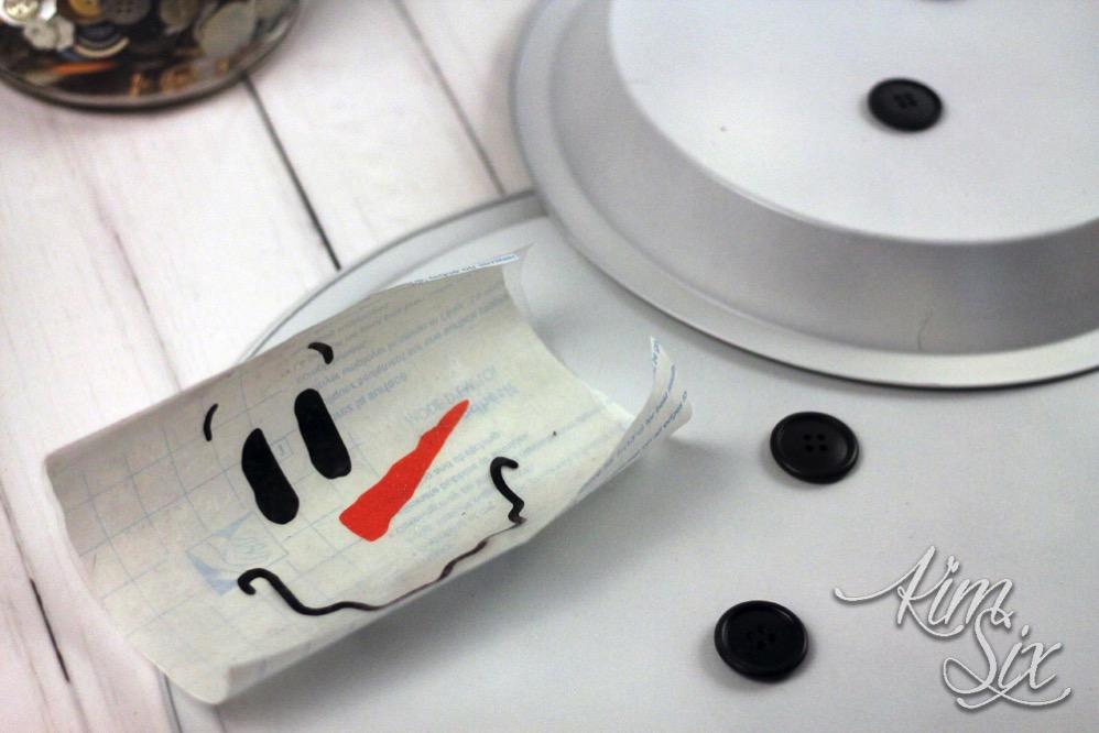 Adding vinyl letters to pie pan snowman