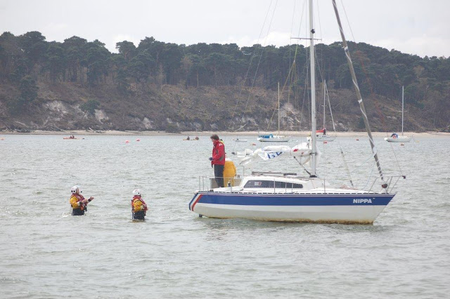 Two ILB crew members walk towards a yacht wedged on the sandbank between the Wych and Main Channels in Poole Harbour - 21 April 2013.  Photo credit: Dave Riley