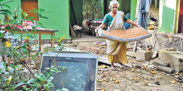 A 65-year-old woman named Ponnamma, who lives alone in Chengannur, India, removes household items that were destroyed in the floods at Thiruvanvandoor in August 2018. Photo: B P Deepu / Express News Service