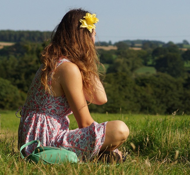 girl sitting in summer meadow