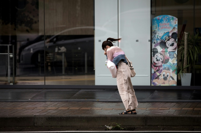 A woman in Tokyo leans into the winds of Typhoon Trami, 30 September 2018. Photo: Behrouz Mehri / AFP