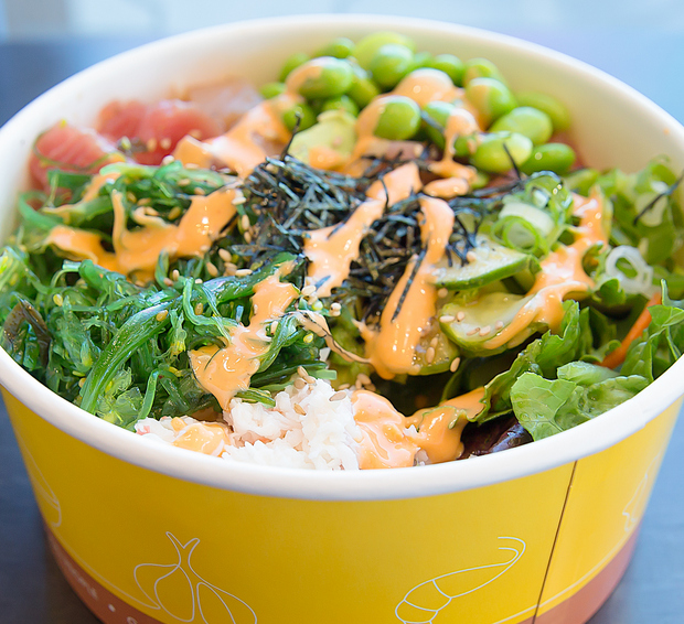 close-up photo of a poke bowl drizzled with spicy mayo sauce