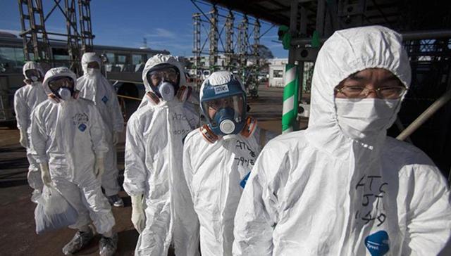 Workers in protective suits and masks wait to enter the emergency operation center at the crippled Fukushima Daiichi nuclear power plant. Photo: Reuters